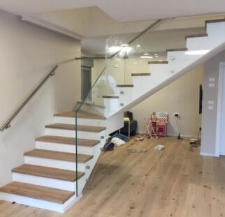 מדרגות בתוך בית עם מעקה מזכוכית