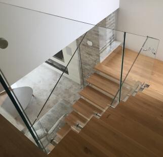 מדרגות עץ בשילוב מעקה מזכוכית בבית פרטי